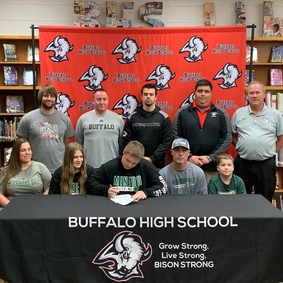 Cody Smith photo with family and coaches.